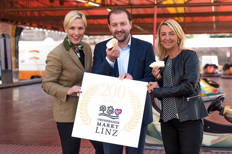 Anke Merkl, Vizebürgermeister Bernhard Baier und Manuela Damm informieren über den Urfahraner Herbstmarkt, der am 30. September beginnt.