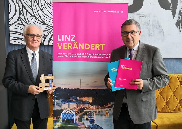 Manfred Grubauer, Vorsitzender des Tourismusverbandes Linz, (l.) mit dem EU-Award und Tourismusdirektor Georg Steiner freuen sich über den Nächtigungsrekord 2018