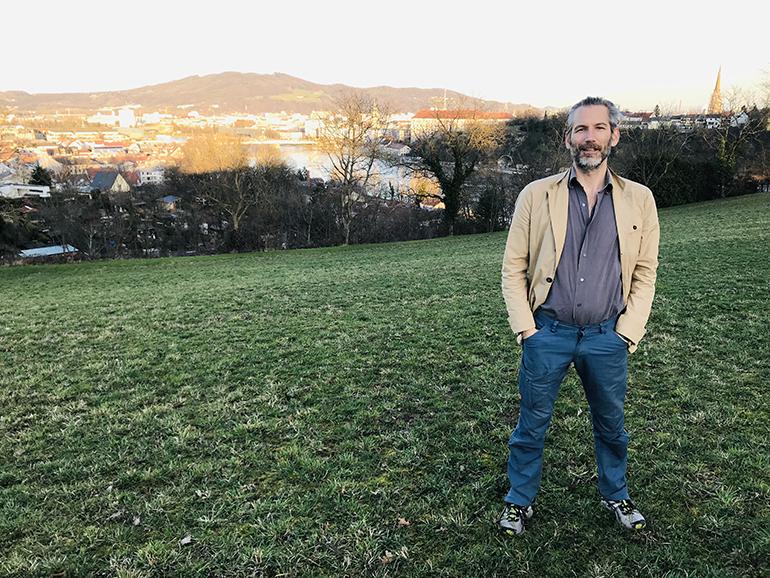 """Lorenz Potocnik auf der Wiese hinter dem Spatzenbauern, die künftig als urbaner Campingplatz genutzt werden könnte: """"Ein einzigartiger Fleck!"""""""
